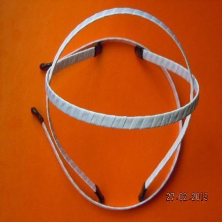 Обруч  металический  0,7 мм.  Обплетён  белой   атласной  лентой  и  заделан  пластмасовыми  наконечниками .
