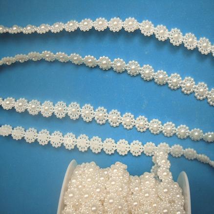 Тесьма сплошная пластиковая из цветочков 10 мм. молочно - кремового цвета  на  нитке.  Цена - 14 грн. за метр.
