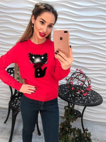 Красный вязаный свитер декорирован аппликацией и стразами.