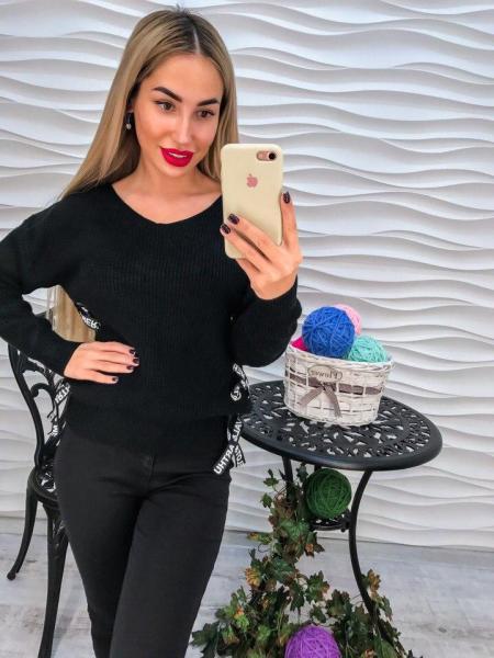 Стильный вязаный черный свитер декорирован лентами.