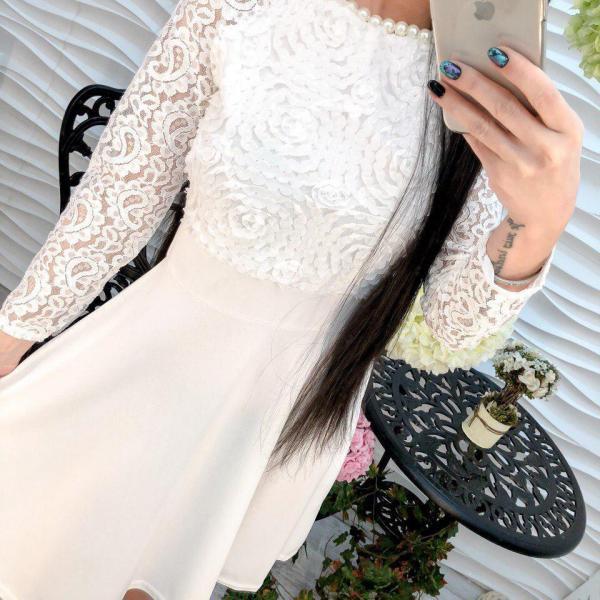 Женское стильное белое платье декорировано лентами.