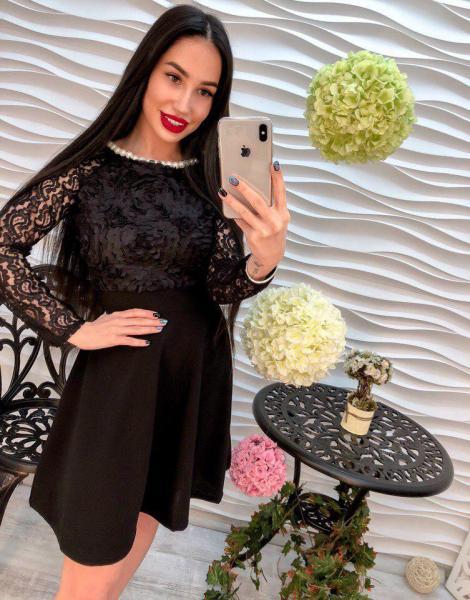 Женское стильное черное платье декорировано лентами.