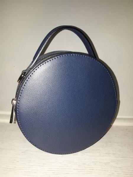 Кругла шкіряна сумка синього кольору має коротку і довгу ручку через плече