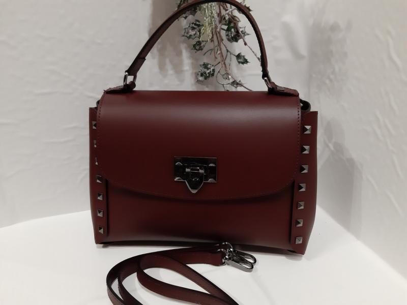 Жіноча шкіряна сумка бордового кольору на короткій і довгій ручці по бокам заклепки на одне відділення