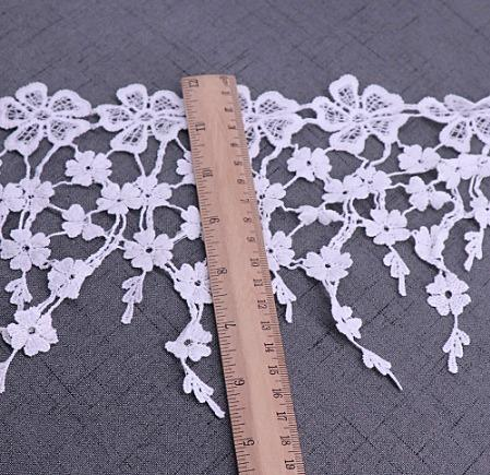 Фото Новинки Кружево  вышитое , цветочки , ширина  185 мм.  Белое  с  кисточками .